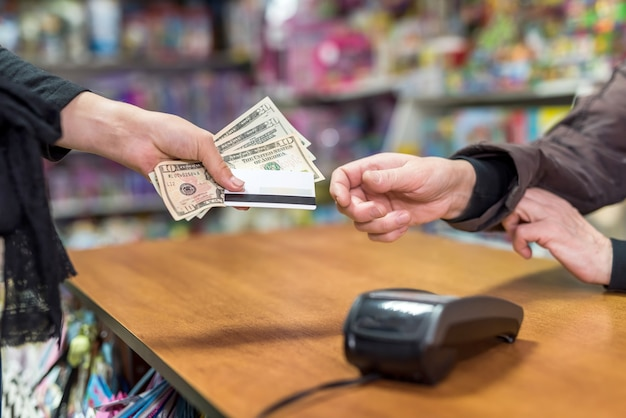 Kobieca ręka dająca dolary i kartę kasjerowi jako płatność