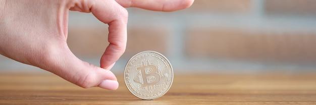 Kobieca ręka dająca kliknięcie zbliżenie srebrnej monety bitcoin