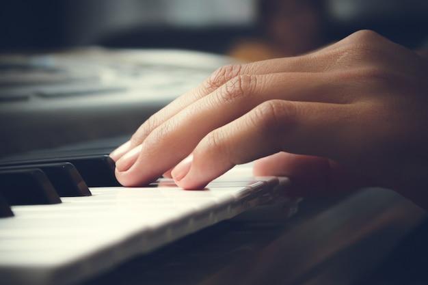 Kobieca ręka dotyka klawiszy fortepianu