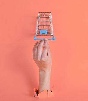 Kobieca ręka dotyka mini wózka na zakupy przez podarty różowy papier. minimalistyczna koncepcja zakupów