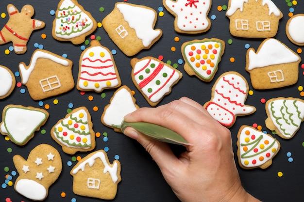 Kobieca ręka farbą zdobi świąteczne ciasteczka