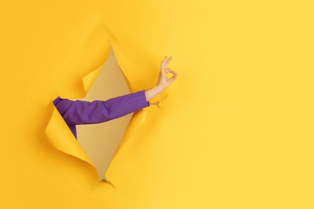 Kobieca ręka gestykulująca w rozdartym żółtym tle dziury w papierze