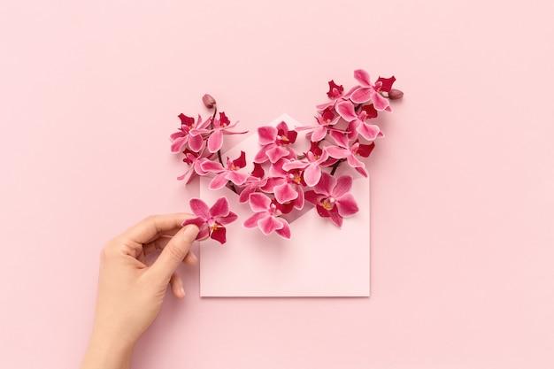 Kobieca ręka i kwiaty orchidei w różowej kopercie jako prezent na dzień matki. leżał na płasko.