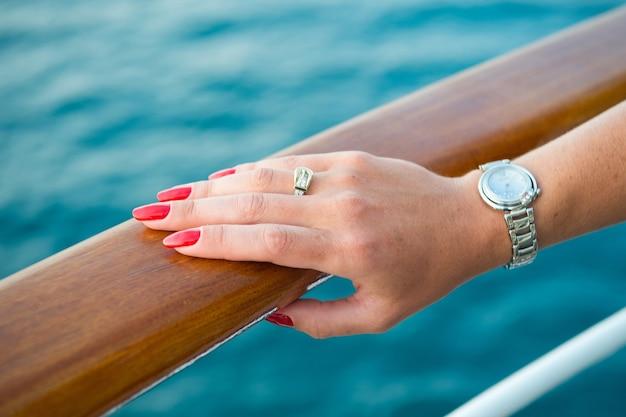Kobieca ręka i zegarek na rękę z czerwonym manicure i złotym pierścionkiem na palcu z diamentami w pobliżu wody