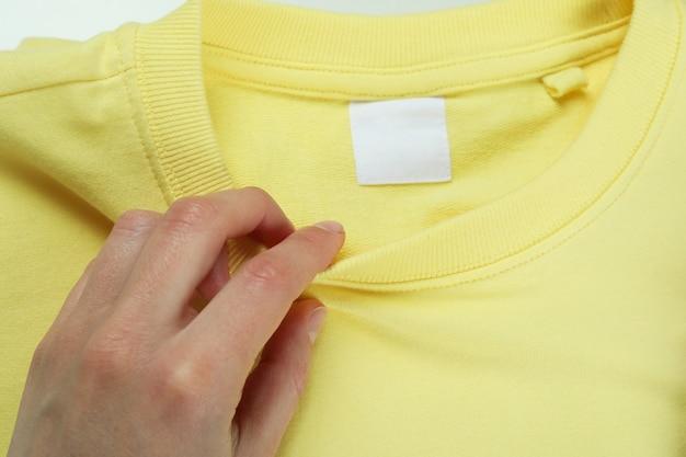 Kobieca ręka i żółta bluza, z bliska