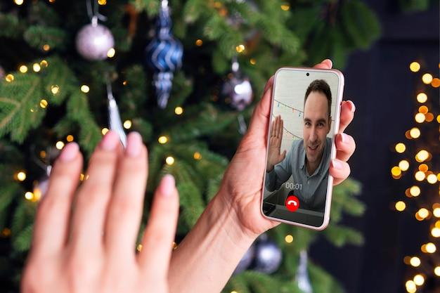 Kobieca ręka macha pozdrowienia na ekranie smartfona na tle choinki. koncepcja pozdrowienia w internecie. koronawirus i kwarantanna na nowy rok.