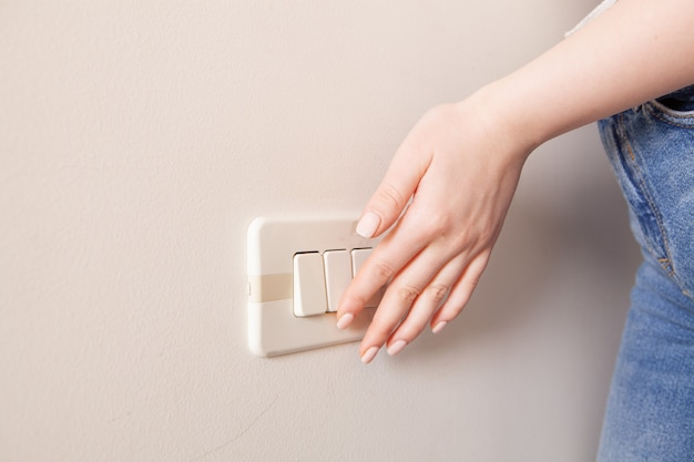 Kobieca ręka naciska przełącznik na ścianie. zapisywanie mediów