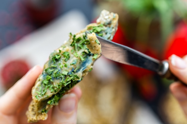 Kobieca ręka nakładająca nożem cebulę na surowy wegański chleb