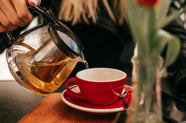 Kobieca ręka nalewa herbatę ze szklanego czajnika do filiżanki w ulicznej kawiarni