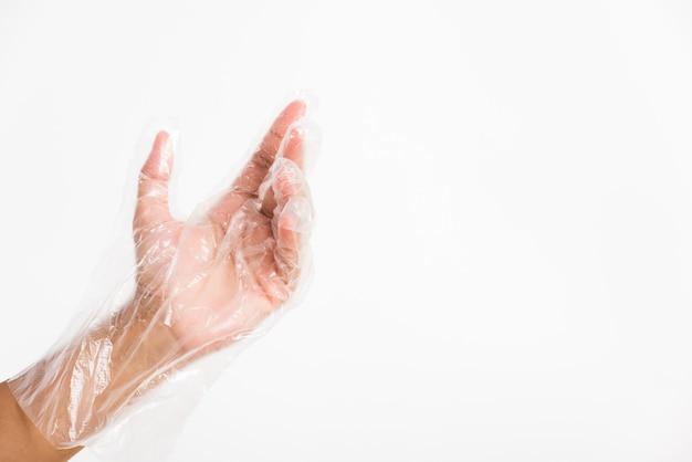 Kobieca ręka nosząca jednorazową rękawicę z tworzywa sztucznego