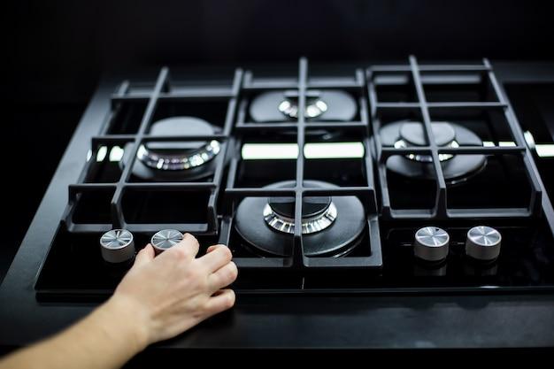 Kobieca ręka obraca uchwyt nowej nowoczesnej kuchenki gazowej z czterema palnikami do kuchni ze stali nierdzewnej
