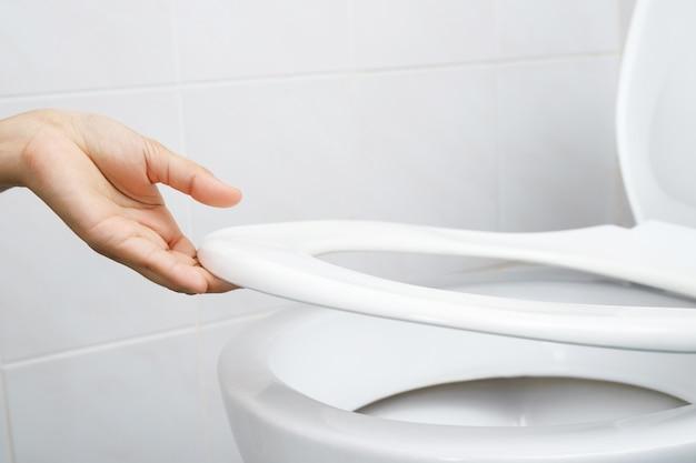 Kobieca ręka otwierająca pokrywę toalety