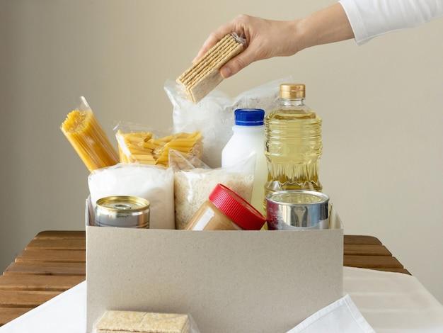 Kobieca ręka pakuje jedzenie do pudełka.