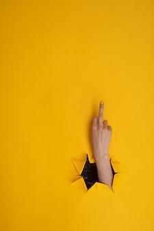 Kobieca ręka pokazująca środkowy palec, kurwa na żółtym tle. gesty rąk