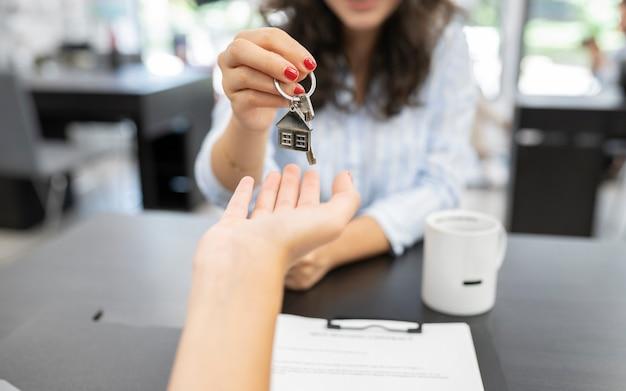 Kobieca ręka przekazująca klucz do domu, koncepcja zakupu domu