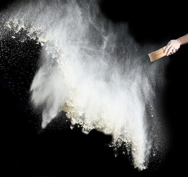 Kobieca ręka przesiewa mąkę pszenną przez okrągłe drewniane sito
