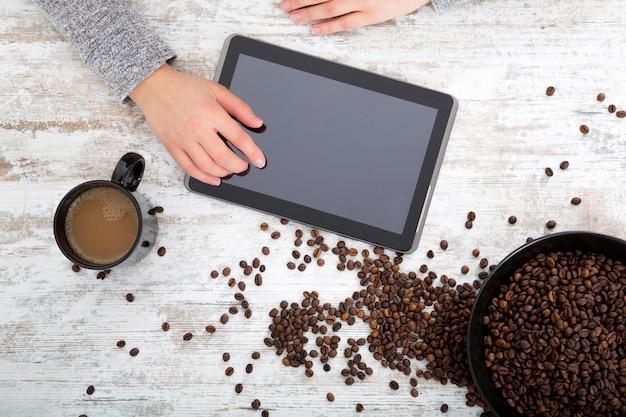 Kobieca ręka przy stole z kawą i tabletem