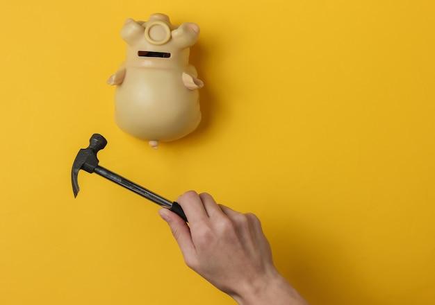 Kobieca ręka rozbija skarbonkę młotkiem na żółtym tle minimalistic concept