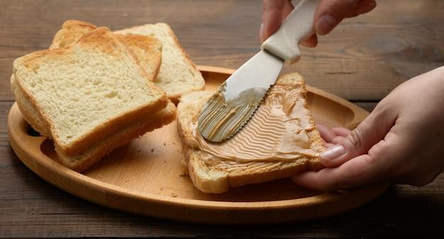 Kobieca ręka rozprowadza masło orzechowe na kwadratowym kawałku białej mąki pszennej, śniadanie