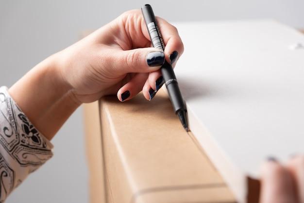Kobieca ręka rysuje prostą linię przed wycięciem nożem okienka na podświetlanym pudełku z pustym miejscem na tekst