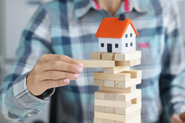 Kobieca ręka słucha drewnianych klocków, na których stoi domek z zabawkami. nieautoryzowana budowa domów i koncepcja jej konsekwencji