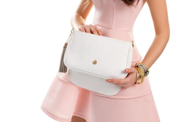 Kobieca ręka trzyma białą torbę. zegarek na rękę i cienkie bransoletki. bawełniana sukienka i skórzana torebka. nowa łososiowa sukienka z biżuterią.