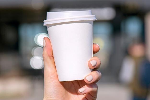 Kobieca ręka trzyma biały papierowy kubek z kawą lub herbatą z rozmytym tłem ulicy