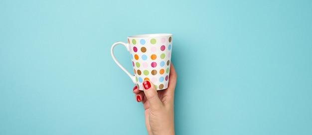 Kobieca ręka trzyma ceramiczny kubek na niebieskim tle, przerwa i picie kawy, baner
