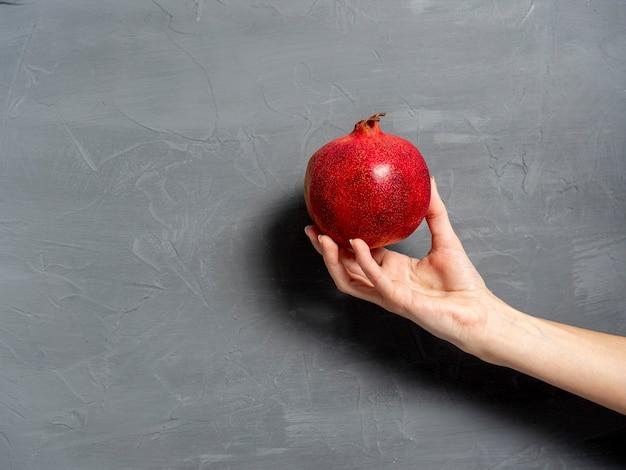 Kobieca ręka trzyma dojrzały soczysty owoc granatu cały na szarym tle. zdrowe i smaczne owoce. skopiuj miejsce.