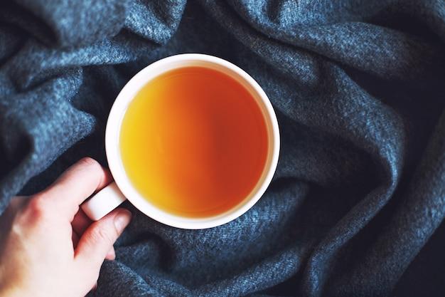 Kobieca ręka trzyma filiżankę z herbatą