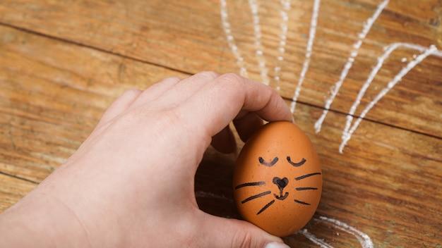 Kobieca ręka trzyma jajko z uroczą buzią. uszy rysowane kredą na drewnianym tle. koncepcja wielkanocy. pocztówka świąteczna