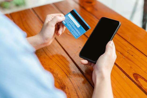 Kobieca ręka trzyma kartę płatniczą i używa smartfona