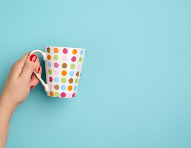 Kobieca ręka trzyma kubek ceramiczny na niebieskim tle, przerwę i picie kawy, kopiowanie miejsca