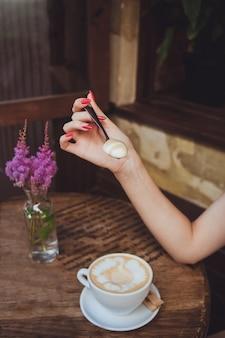 Kobieca ręka trzyma łyżkę z mleczną pianką z kawy, kubek, którym stoi na drewnianym stole ze szklanym wazonem z gałązkami różowych kwiatów astilbe i zielonych liści.