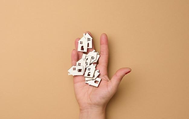 Kobieca ręka trzyma miniaturowe drewniane domy. koncepcja wyszukiwania nieruchomości do wynajęcia, hipoteki, ubezpieczenia nieruchomości