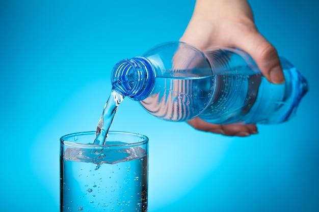 Kobieca ręka trzyma plastikową butelkę i nalewa wodę do szklanki na jasnoniebieskim tle.