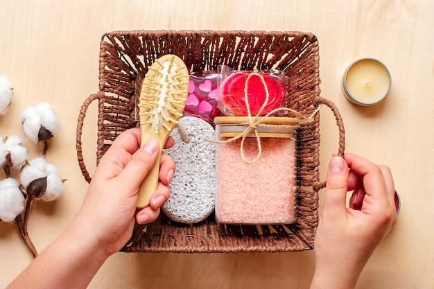 Kobieca ręka trzyma pudełko pielęgnacyjne zestaw ekologicznych kosmetyków