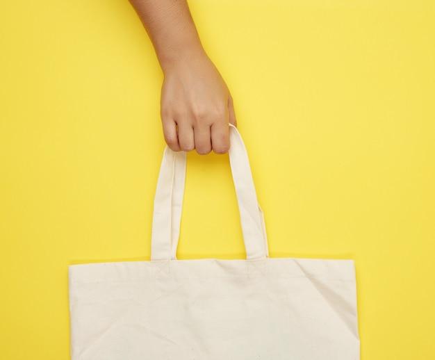 Kobieca ręka trzyma pustą beżową torbę tekstylną za uchwyty na żółtej powierzchni