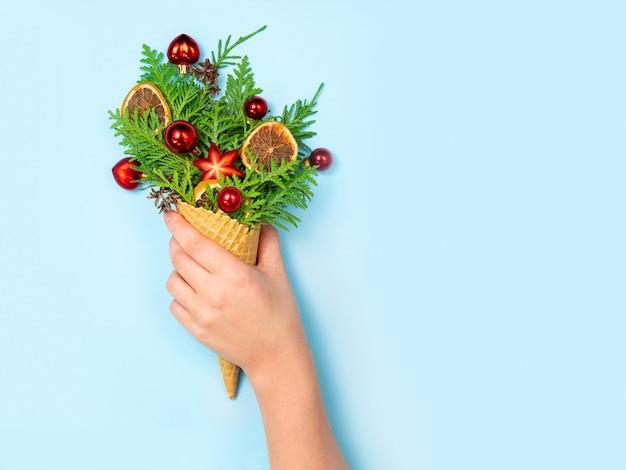 Kobieca ręka trzyma róg faweli z gałązkami tui i zabawkami świątecznymi na niebiesko.