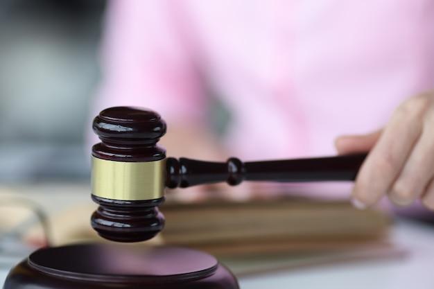 Kobieca ręka trzyma sędziów drewniany młotek koncepcja systemu sądowniczego