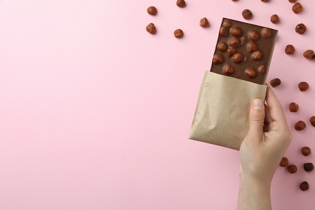 Kobieca ręka trzyma smaczną czekoladę na różowym tle