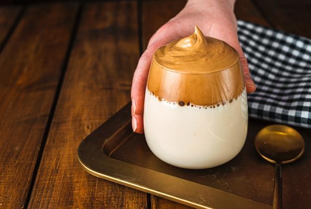 Kobieca ręka trzyma szklankę bitej kawy rozpuszczalnej dalgona