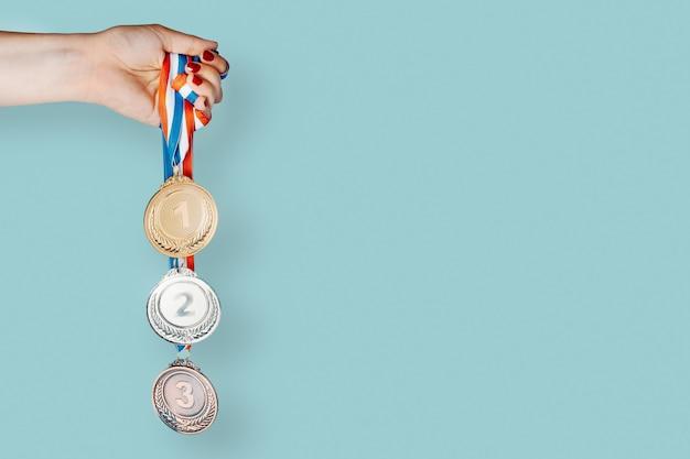 Kobieca ręka trzyma trzy medale (złoto, srebro, brąz). koncepcja nagrody i zwycięstwa. skopiuj miejsce