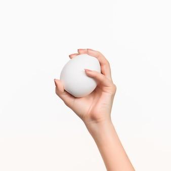 Kobieca ręka trzymająca biały pusty styropianowy owal