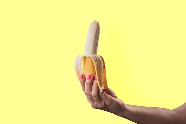 Kobieca ręka trzymająca dojrzałego banana na żółtym tle