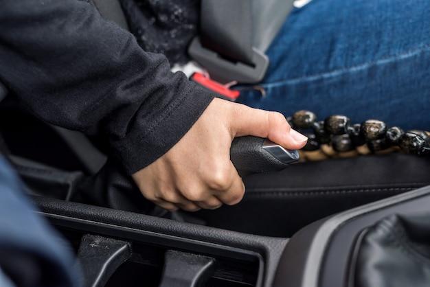 Kobieca ręka trzymająca dźwignię hamulca ręcznego wewnątrz samochodu