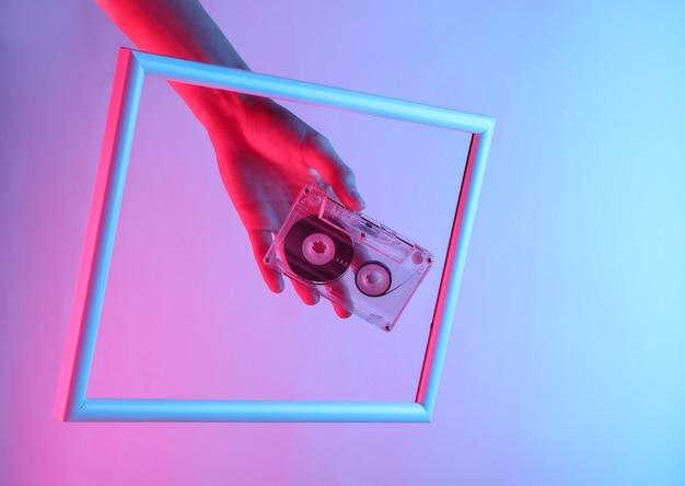 Kobieca ręka trzymająca kasetę audio przez strzelistą ramkę z neonowym światłem holograficznym