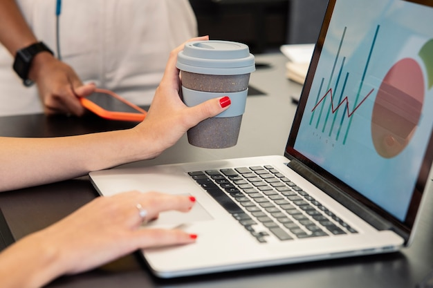 Kobieca ręka trzymająca kawę podczas korzystania z komputera