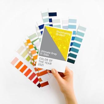 Kobieca ręka trzymająca kolory roku 2021 - ultimate grey i illuminating z modnymi próbkami kolorów. paleta trendów kolorystycznych.