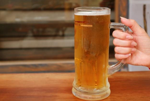 Kobieca ręka trzymająca kufel schłodzonego piwa na drewnianym stole